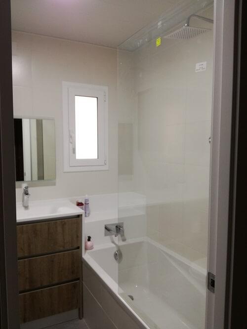 Baño después de la reforma en blanco y con parquet.