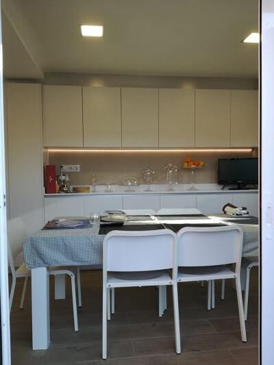 Cocina reformada en blanco con parquet.